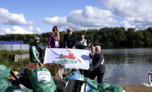 Grupa wolontariuszy z banerem Kajakowy Ekopatrol z workami śmieci zebranymi z Odry