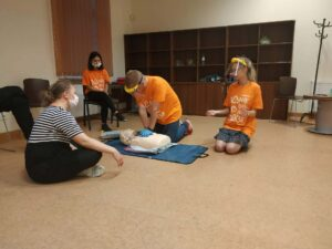 4 osoby siedzące na podłodze z fantomem podczas szkolenia z pierwszej pomocy